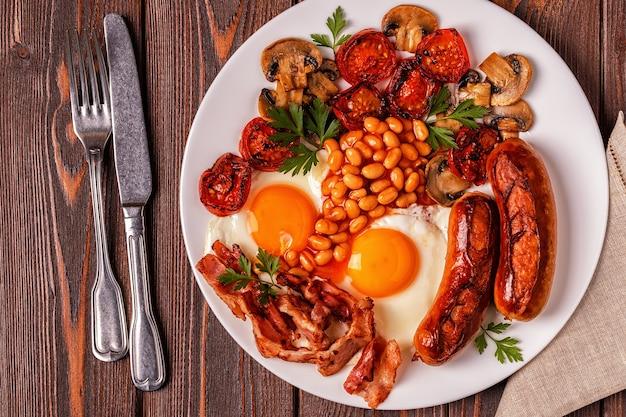 Petit-déjeuner anglais complet traditionnel avec des œufs au plat, des saucisses, des haricots, des champignons, des tomates grillées et du bacon sur fond de bois