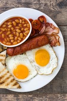 Petit-déjeuner anglais complet traditionnel avec des œufs au plat, des saucisses, des haricots, des champignons, des tomates grillées et du bacon sur une surface en bois.