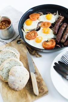 Petit déjeuner anglais dans une casserole sur un fond blanc.