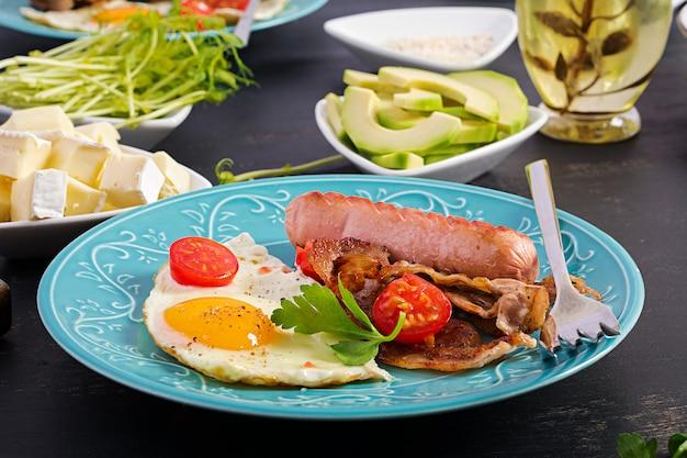 Petit déjeuner anglais - œuf au plat, tomates, saucisses et bacon.