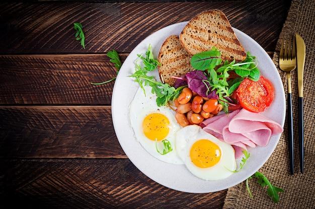 Petit-déjeuner anglais - œuf frit, haricots, tomates, saucisses, jambon et pain grillé