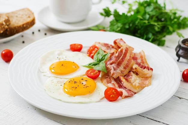 Petit-déjeuner anglais - œuf frit, tomates et bacon.