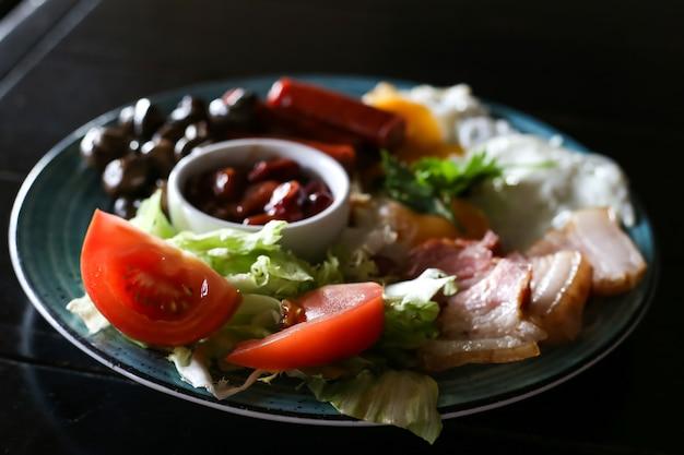 Petit-déjeuner anglais avec œufs au plat, saucisses, bacon, haricots