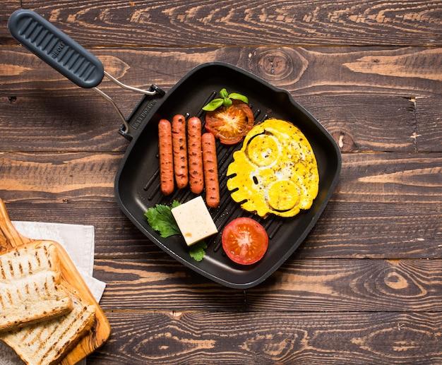 Petit-déjeuner anglais, œufs au plat, saucisses, haricots, toasts, tomates, fromage sur une table en bois,