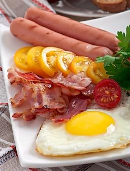 Petit-déjeuner anglais - œufs frits, bacon, saucisses et pain de seigle grillé