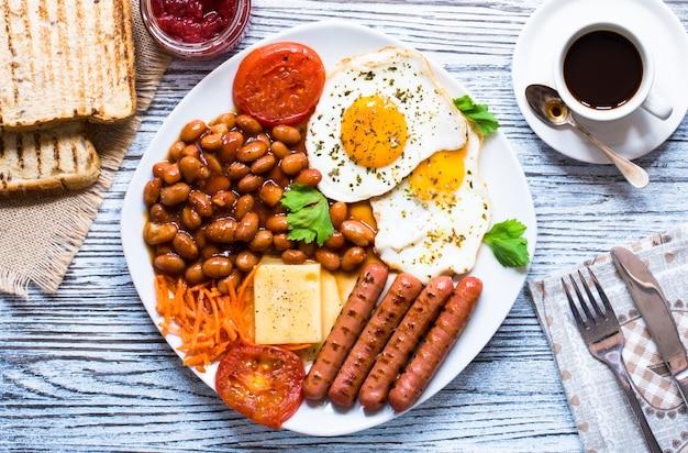 Petit déjeuner anglais. oeufs sur plat saucisses haricots pain toasts tomates fromage sur un fond en bois