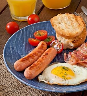 Petit déjeuner anglais - pain grillé, oeuf, bacon et légumes dans un style rustique sur table en bois