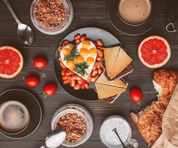 Petit déjeuner anglais. saucisse, œufs au plat et haricots à la tomate. café et pain à proximité. chia au yaourt et granola
