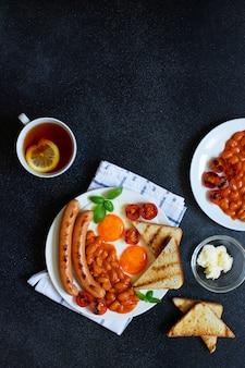 Petit déjeuner anglais avec saucisses frites, haricots, champignons, œufs frits, tomates cerises grillées. servi avec une tasse de thé au citron, pain grillé et beurre. fond noir, vue de dessus, fond