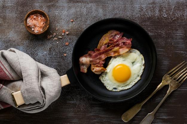 Petit-déjeuner anglais traditionnel avec œufs au plat et bacon dans une poêle en fonte sur fond de béton foncé. vue de dessus.