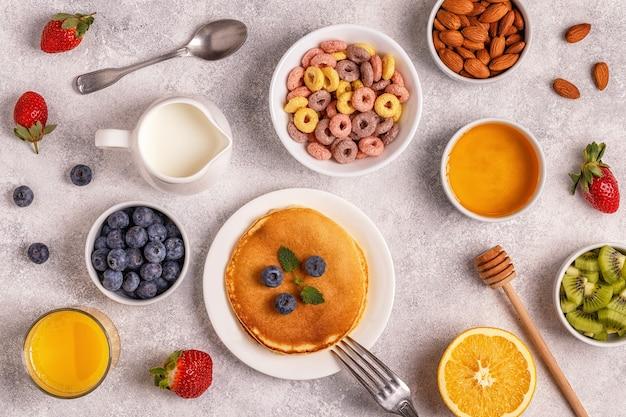 Petit-déjeuner avec anneaux de céréales colorés, crêpes, fruits, lait, jus. vue de dessus.