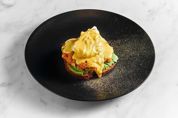Petit-déjeuner appétissant et sain - pain grillé à l'avocat, tomates au four, œuf poché et sauce hollandaise, servi dans une assiette noire sur une surface en marbre