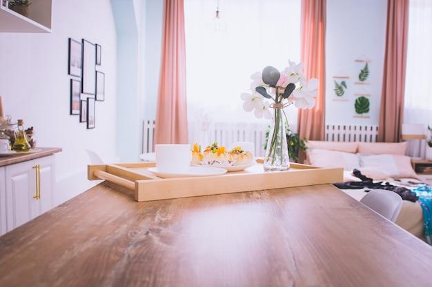 Petit-déjeuner au lit avec café, brioches, fleurs sur plateau en bois dans un lit d'hôtel ou à la maison. lumière de fenêtre
