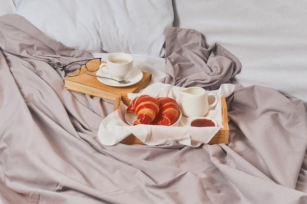 Petit déjeuner au lit, café, livre, croissants avec confiture