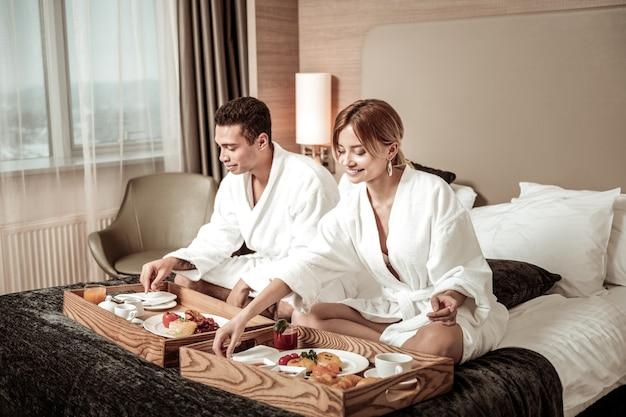 Petit déjeuner au lit. couple d'hommes d'affaires se sentant détendu tout en prenant un délicieux petit déjeuner au lit