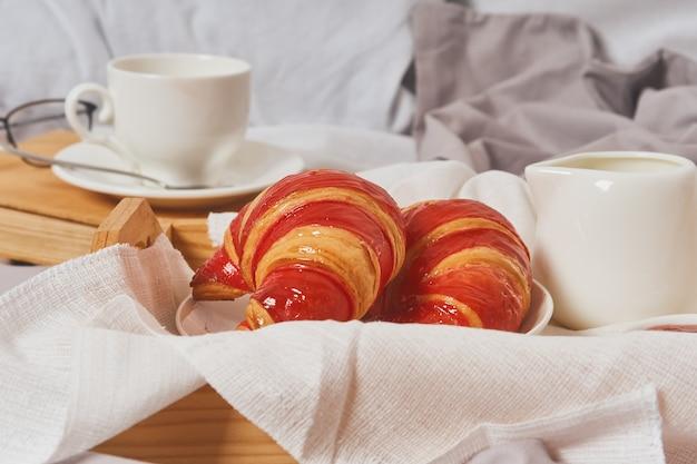 Petit-déjeuner au lit avec expresso, fleur et croissant