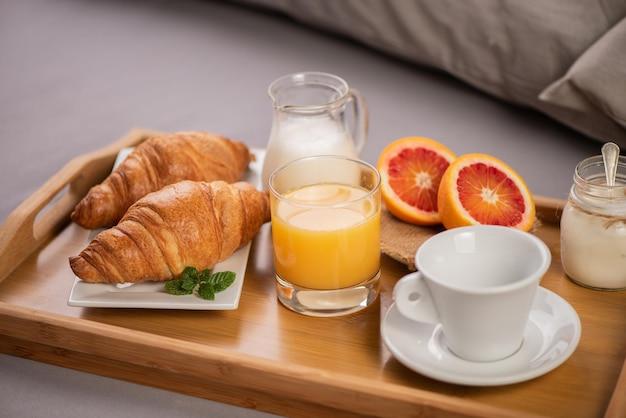 Petit-déjeuner au lit avec des fruits à l'orange et des pâtisseries sur un plateau en gros plan