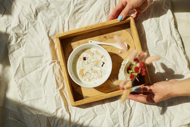 Petit-déjeuner au lit, les mains des femmes essaient avec un bol de muesli, du granola et des fleurs au soleil à la maison, femme de chambre apportant un plateau avec petit-déjeuner dans la chambre d'hôtel, bon service