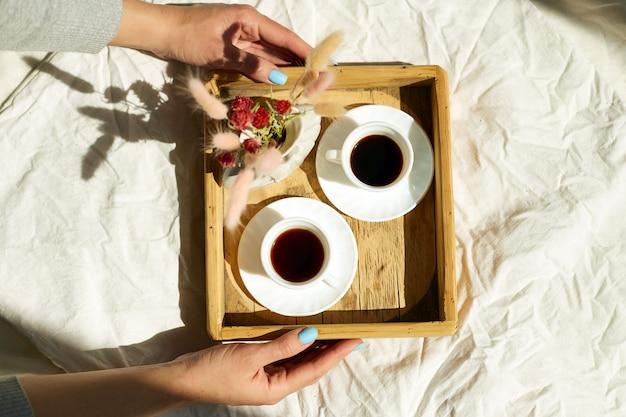 Petit-déjeuner au lit, les mains des femmes essaient avec deux tasses de café et des fleurs au soleil à la maison, femme de chambre apportant un plateau avec petit-déjeuner dans la chambre d'hôtel, bon service