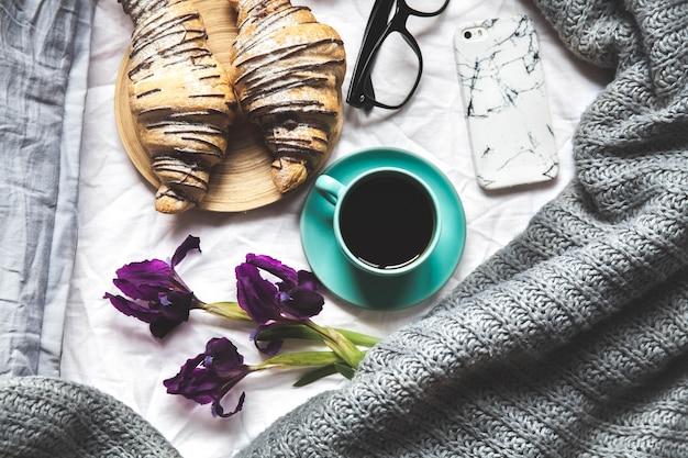 Petit déjeuner au lit. matin, croissant, café, fleurs et un cahier avec un stylo. planification