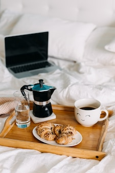 Petit déjeuner au lit avec un ordinateur portable