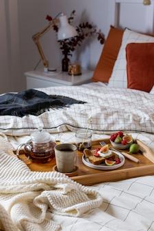 Petit déjeuner au lit avec pâtisserie et fruits frais, thé noir