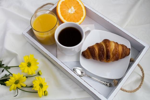 Petit-déjeuner au lit sur le plateau en bois blanc