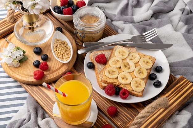 Petit déjeuner au lit. plateau en bois avec verre de jus d'orange et sandwich aux fruits rouges