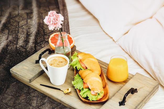 Petit déjeuner au lit sur un plateau en bois