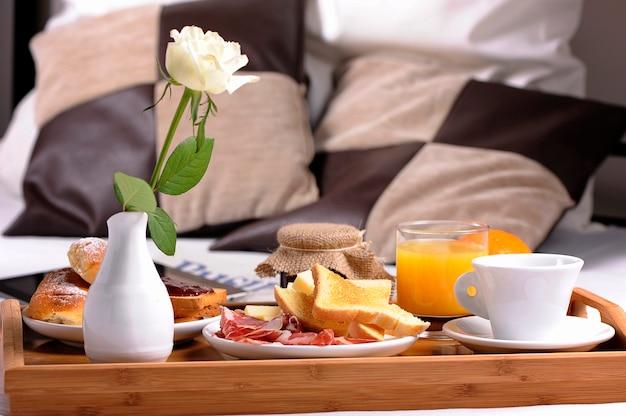 Petit déjeuner au lit. plateau avec café, croissants et fruits