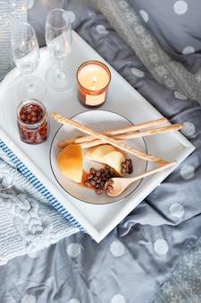 Petit-déjeuner au lit, un plateau avec du fromage, des grissini, de la confiture de jeunes pommes de pin, du champagne et une bougie
