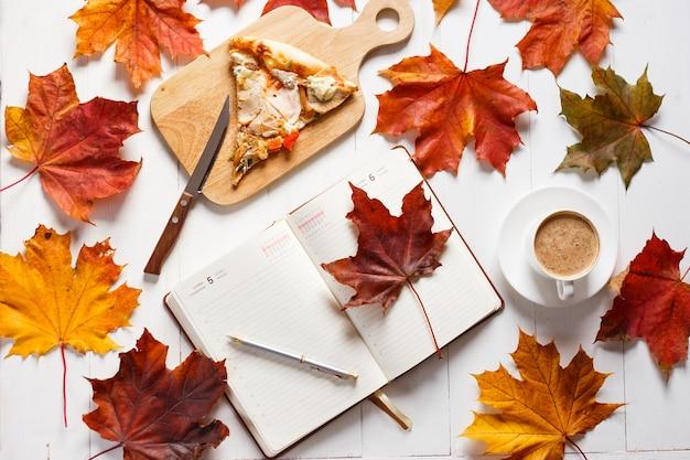 Petit-déjeuner d'automne avec café, pizza et agenda. concept de vue de dessus