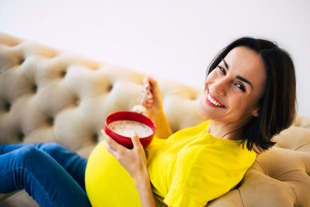 Petit déjeuner aux céréales pour la future maman. photo en gros plan d'une femme enceinte heureuse assise à la maison sur un canapé, mangeant des aliments sains et souriant.