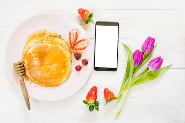 Petit déjeuner aux crêpes avec téléphone portable