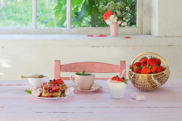 Petit déjeuner aux fraises sur table en bois rose