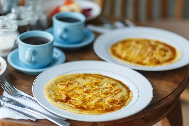 Petit déjeuner balinesse traditionnel avec deux tasses bleues de boisson chaude sur une table en bois.