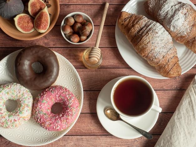 Petit déjeuner beignet croissant figues noix sur les assiettes sur la table