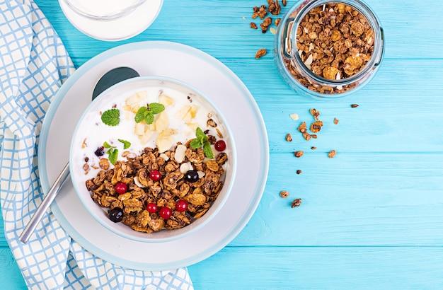 Petit déjeuner. bol de granola fait maison avec du yaourt et des baies fraîches. réglage de la table. la nourriture saine. vue de dessus.