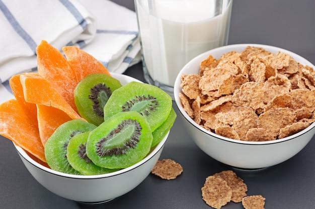 Petit-déjeuner. bols avec cornflakes, kiwi séché et mangue. verre de lait. alimentation équilibrée.