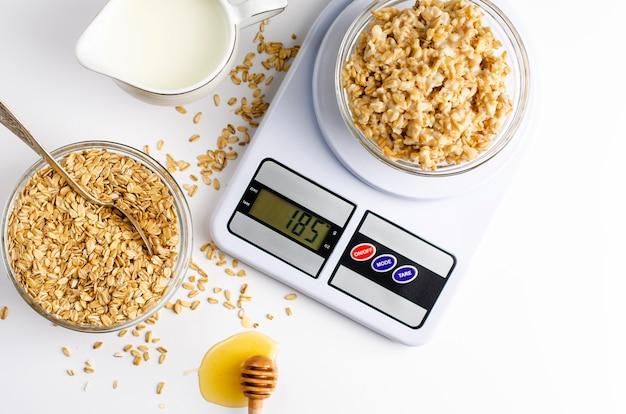 Petit-déjeuner avec bouillie d'avoine sur des balances de cuisine numériques, lait et miel sur blanc