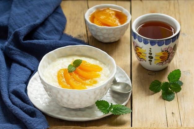 Petit déjeuner de bouillie de riz avec confiture de pêches et thé. style rustique, mise au point sélective.