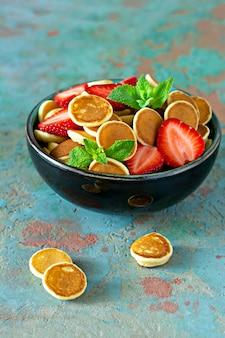 Petit-déjeuner branché à la maison avec de minuscules crêpes (mini crêpes) aux fraises et à la menthe dans un bol (tasse) sur fond bleu.