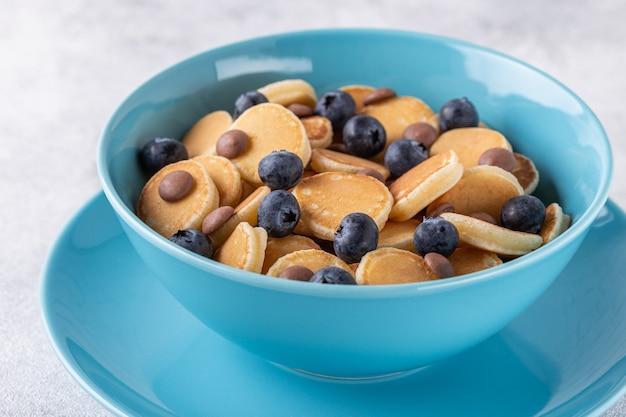 Petit-déjeuner branché avec mini crêpes, myrtilles et pépites de chocolat, vue de dessus.