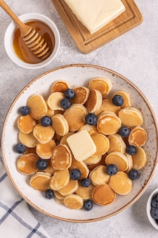 Petit-déjeuner branché avec mini crêpes et myrtilles, vue du dessus.