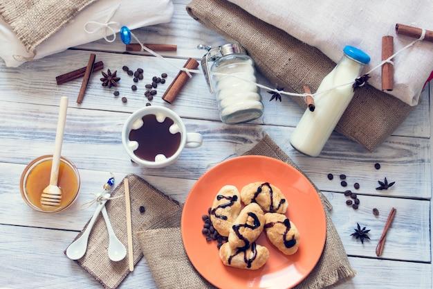 Petit déjeuner de café, croissants, lait, miel, sucre, cannelle, anis