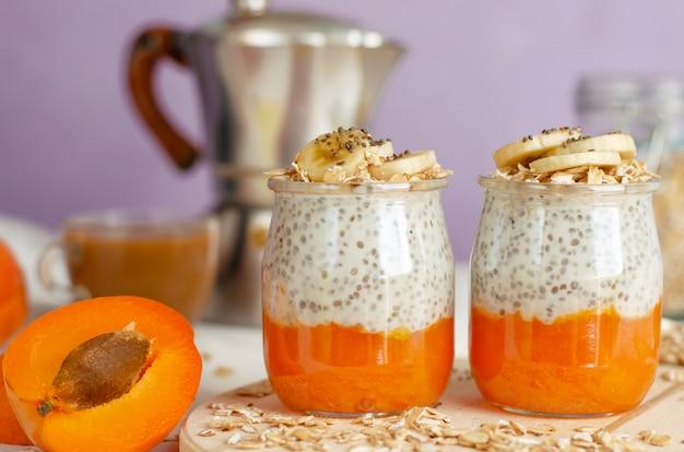 Petit déjeuner avec café, plats d'avoine, pudding aux graines de chia et fruits sur une planche de bois.