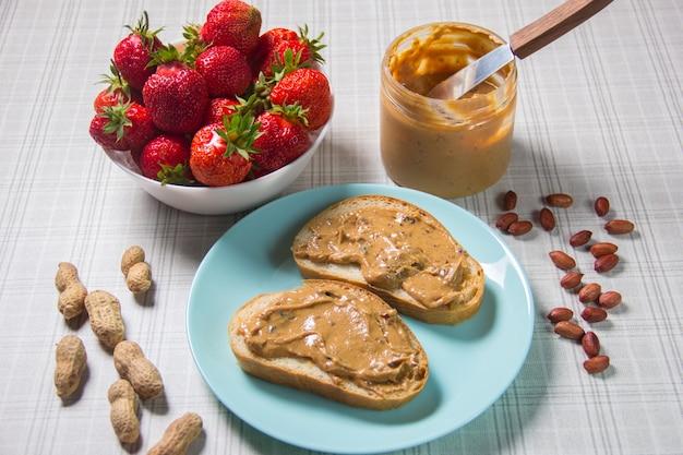 Petit déjeuner avec café et sandwichs avec pâte d'arachide et fraises