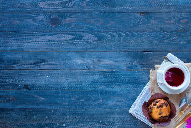 Petit déjeuner avec café et thé avec différentes pâtisseries et fruits sur une table en bois