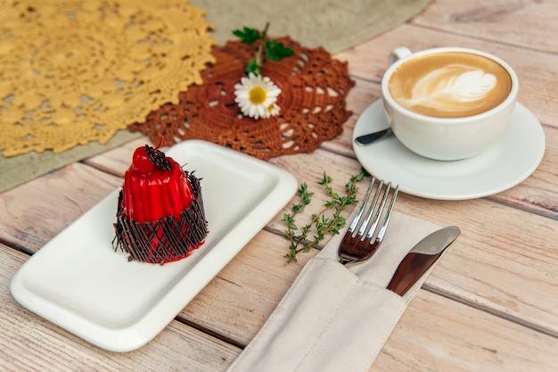 Petit déjeuner avec cappuccino et gâteau sur table en bois avec fourchette et couteau