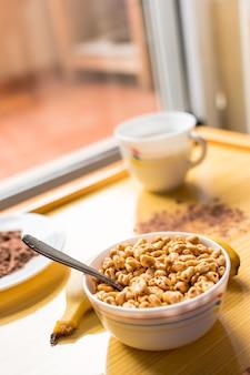 Petit déjeuner avec des céréales dans un bol avec du lait, du cacao et de la banane
